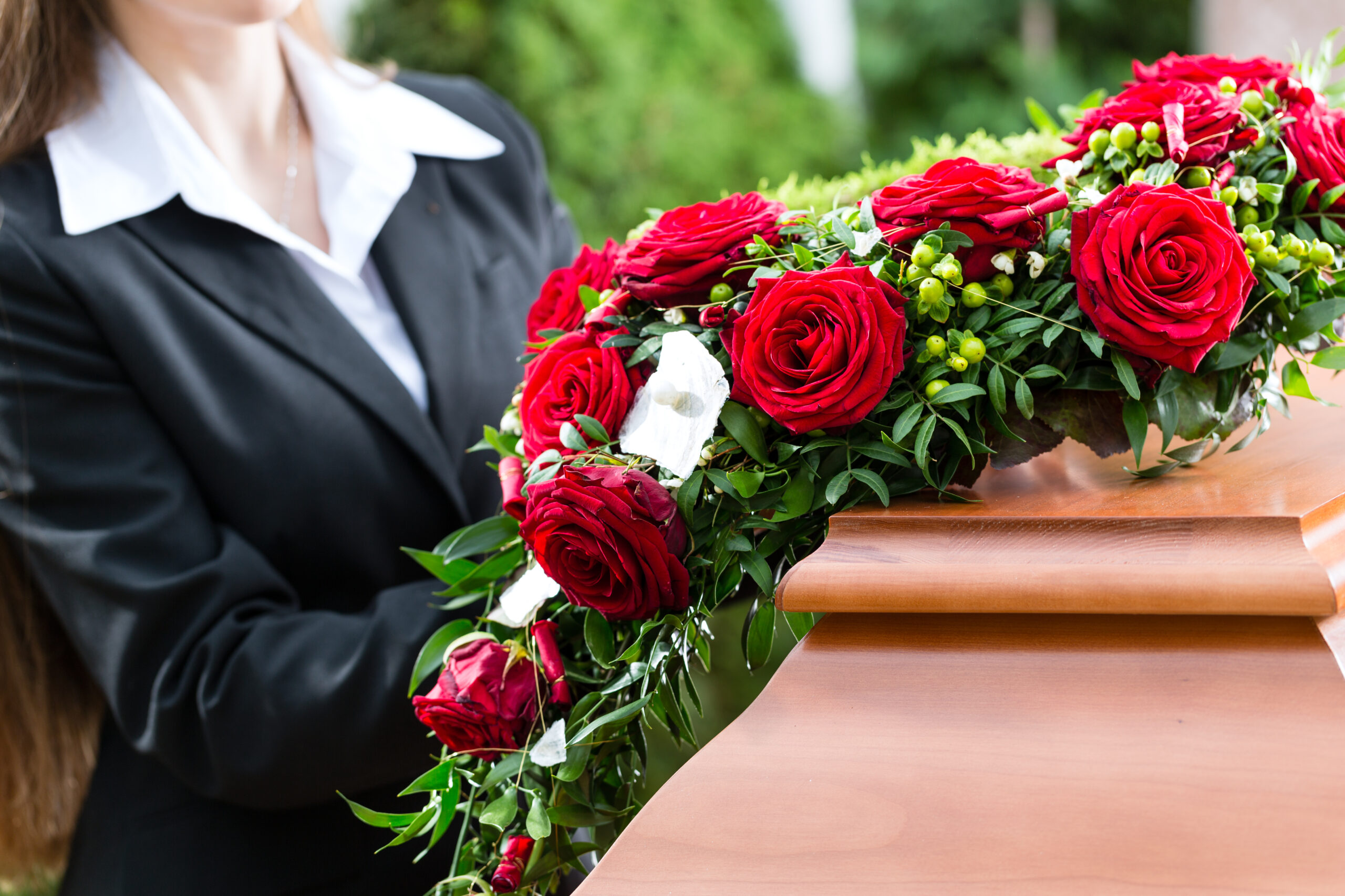 Photo of woman holding rose floral arrangement at a funeral